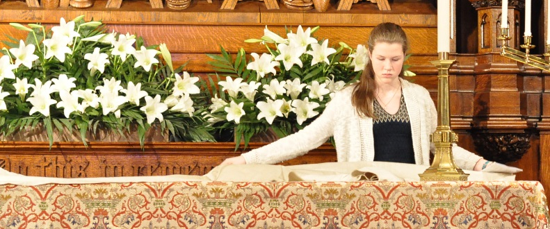 Young woman unfolds protective cover for altar