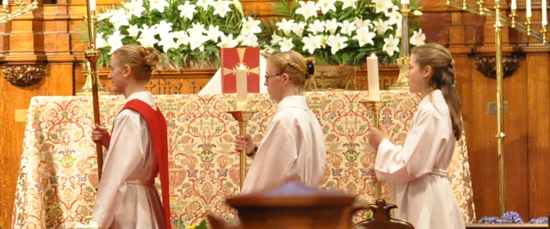 Three young women process in acolyte robes