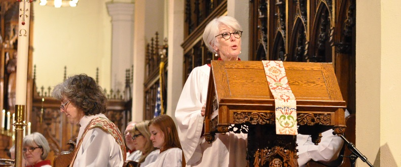 Woman reads at lectern with choir in background