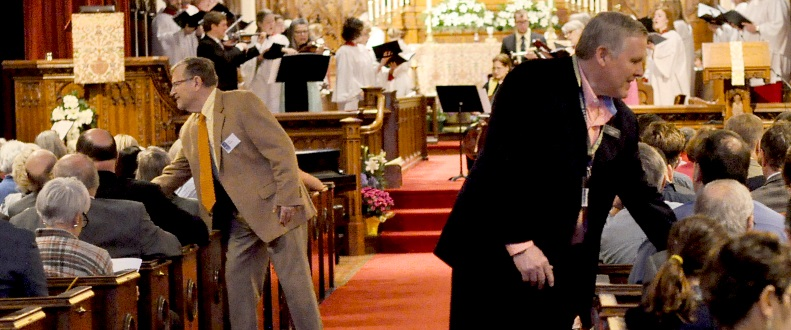 Men interact with seated parishoners