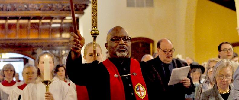 Solemn man leads church procession