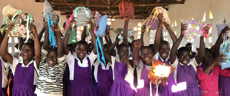 African schoolgirls happily holding up their menstrual kits for the camera