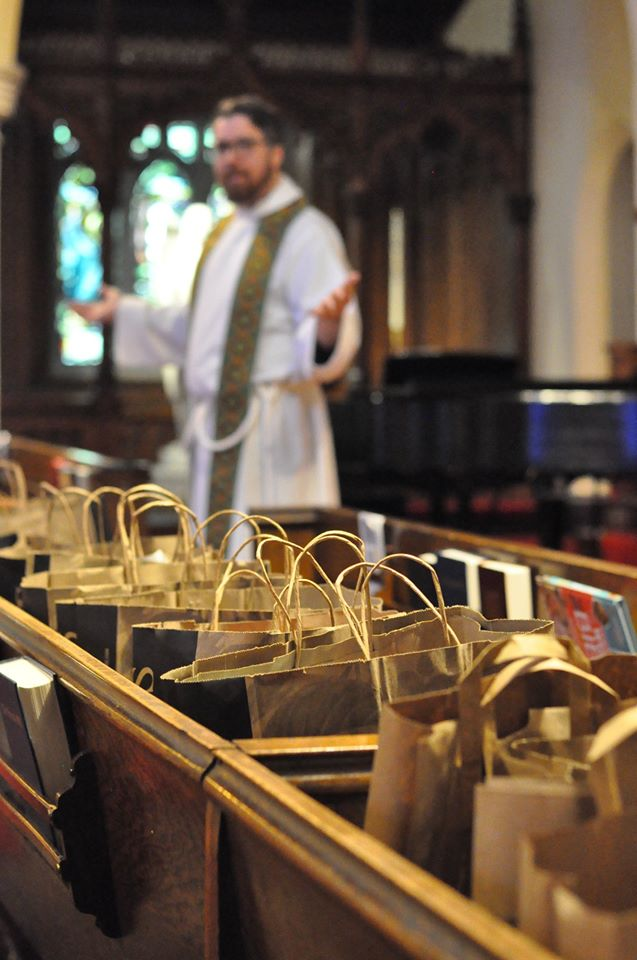 Rows of grocery bags in the pews with Jered preaching in the background
