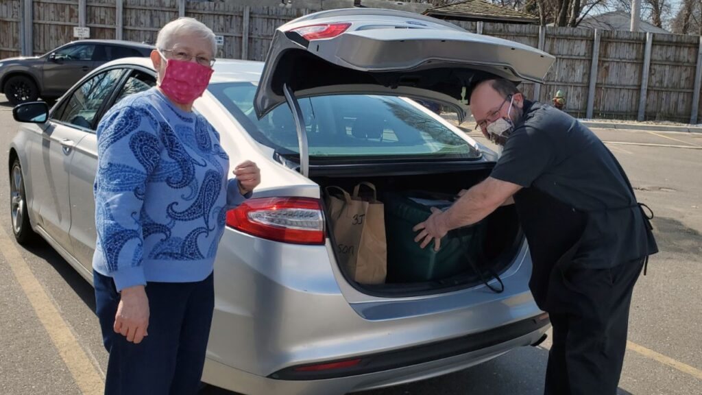 Two people wearing masks loading meals into a car trunk