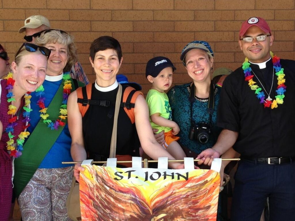 A group of St. John's clergy and parishioners posing for a photo at the Pride Parade