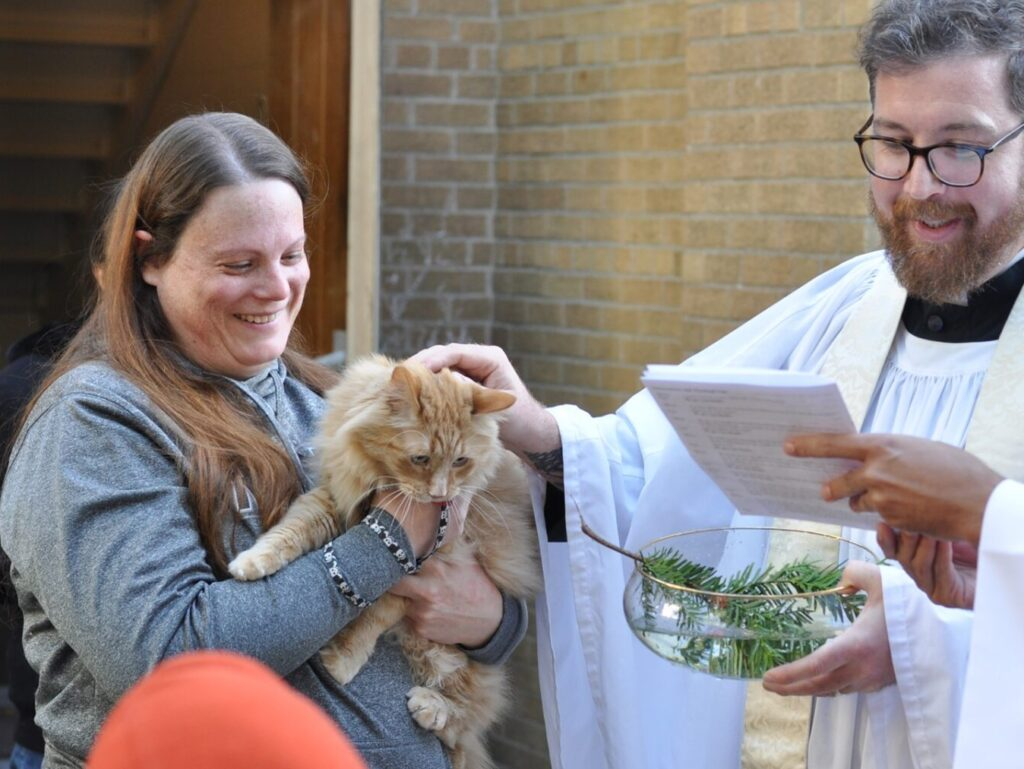 A person holding a cat at the Blessing of the Animals