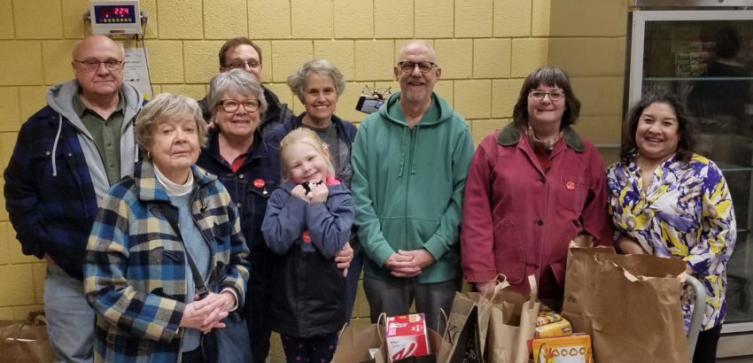 A group of parishioners standing near bags of donated food