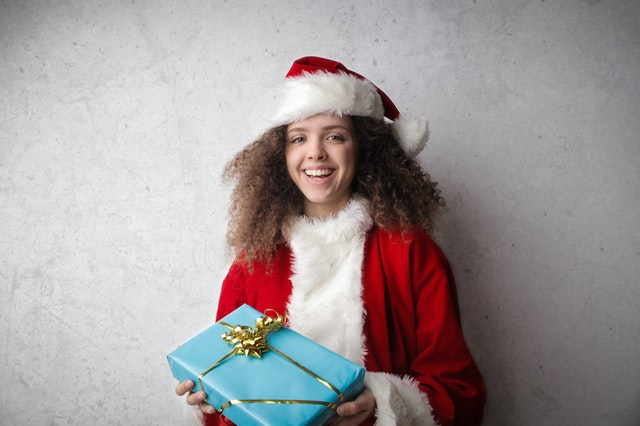 A child dressed as Santa holding a present