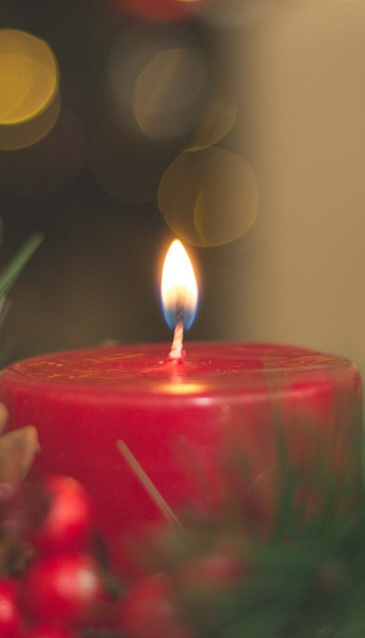 A red candle burning in an Advent wreath