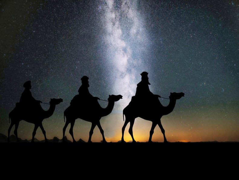 A silhouette of three people riding camels at night